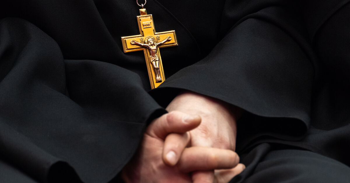 a Catholic priest's hands and a cross
